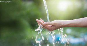 Hand unter Wasserstrahl in Natur
