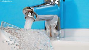 Glas wird unter Wasserhahn mit Trinkwasser befüllt