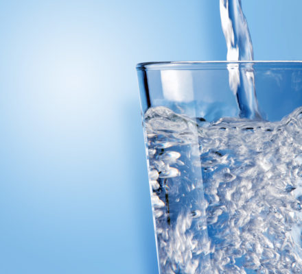 Glas wird mit Wasser befüllt
